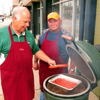 Jim Johnson slices into a slab of baby back ribs he cooked on a Big Green Egg ceramic cooker at a class at Thyme in the Kitchen.