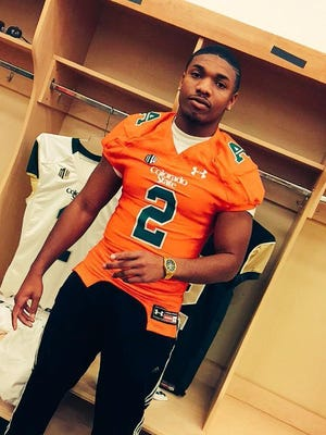 Devron Davis wears a CSU jersey in the Hughes Stadium locker room during a recruiting visit to CSU last winter.
