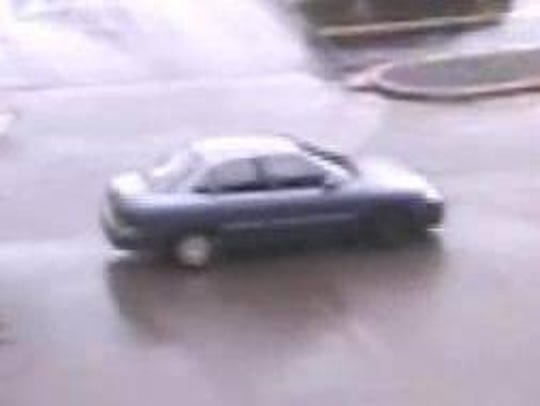 A four-door, blue-gray car with a hubcap missing suspected