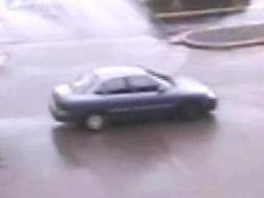 A four-door, blue-gray car with a hubcap missing suspected of being driving by a woman involved in a recent theft is seen on security footage.