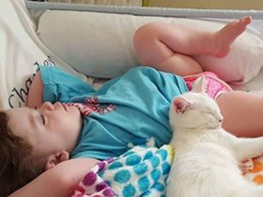 Charley, 4, sleeps with her cat, Angel, who went missing for more than three months before being found on Dec. 10.
