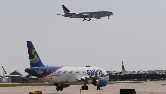 An American Airlines jet prepares to land as a Spirit Airlines jet taxis at O'Hare International Airport.