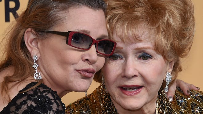 Debbie Reynolds (right), recipient of the Screen Actors Guild Life Achievement Award, and daughter Carrie Fisher pose in the press room during the 21st annual SAG Awards at The Shrine auditorium on Jan. 25, 2015, in Los Angeles.