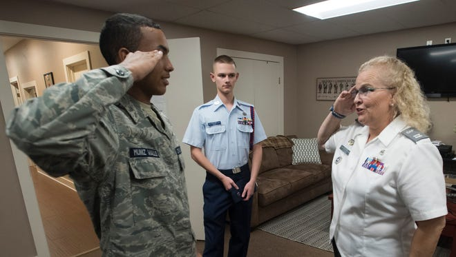 At left, Jaiden Muniz-Walls, a cadet with Pensacola's Civil Air Patrol Cadet Squadron, offers a salute to Capt. Mia Ottesen, right, during the group's meeting on Tuesday, Nov. 7, 2017, at Ferguson Airport as a fellow cadet, Micah Barr, looks on.