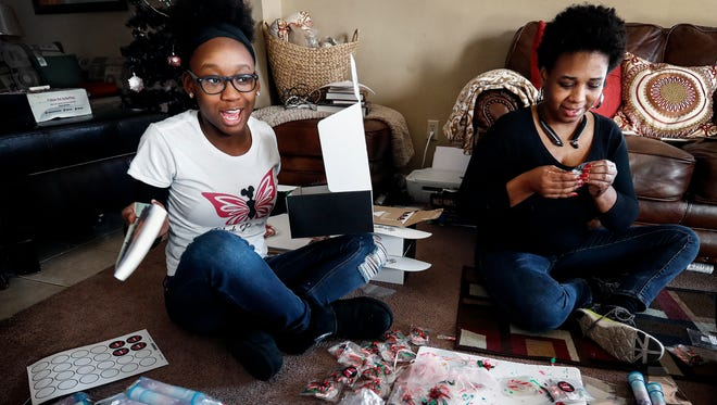 Journi Prewitt, 17, (left) and her mother Shauntay Prewitt (right) place items in Black Butterfly Beautiful subscription boxes at their home Wednesday afternoon. The younger Prewitt came up with the online business that would boost the esteem and self-awareness in black youths. The boxes are sent monthly and include trinkets, books and various products from black female-owned businesses.