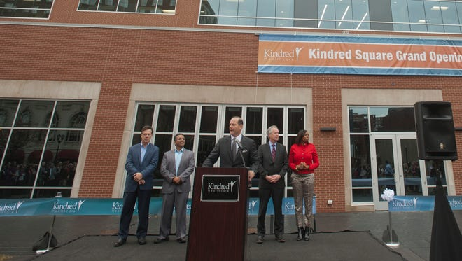 As Kindred Healthcare CEO and President Ben Breier speaks, center, (l-r) John Hopkins Wellness Center General Manager Naren Balkarran, Greater Louisville Inc. CEO Kent Oyler, Mayor Greg Fischer and Nicole Yates, district director for U.S. Congressman John Yarmuth listen as they stand in front of 658 S. Fourth St. at a ribbon-cutting ceremony for Kindred's two new buildings on Thursday, Jan. 11, 2018.