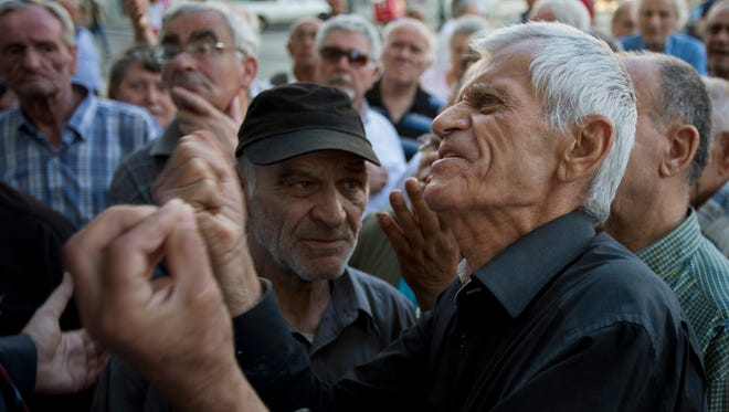 Elderly people argue with a bank worker as they wait to be allowed into the bank to withdraw a maximum of 120 euros ($134) for the week in Athens, Monday, July 6, 2015.