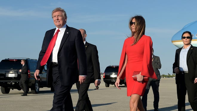 President Trump walks with first lady Melania Trump after she greeted him on the tarmac after he arrived via Air Force One at Palm Beach International Airport in West Palm Beach, Fla., on Feb. 3, 2017.