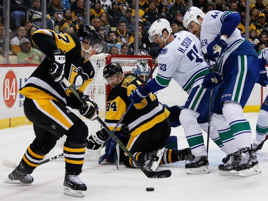 Pittsburgh Penguins' Sidney Crosby (87) looks for an opening in a crowded crease during the second period of an NHL hockey game against the Vancouver Canucks in Pittsburgh, Wednesday, Nov. 22, 2017. (AP Photo/Gene J. Puskar)