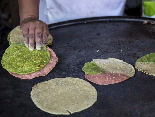 A woman makes tortillas with three kinds of dough made