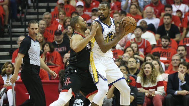 Golden State Warriors forward Kevin Durant (35) moves the ball against Houston Rockets guard Eric Gordon (10) during the first half in game two of the Western conference finals of the 2018 NBA Playoffs at Toyota Center.