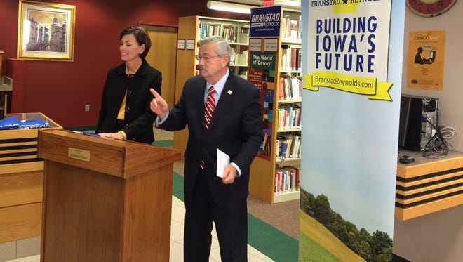 Iowa Gov. Terry Branstad, right, speaks to voters at the Adel Public Library on Thursday. Lt. Gov. Kim Reynolds is at left.