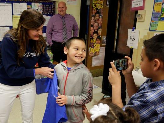 A smiling Mateo Meza, 9, center, a Grant Elementary