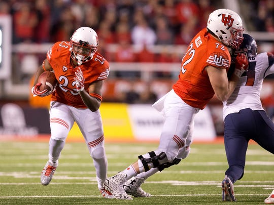 Utah offensive lineman Garett Bolles (second from right) clears a hole for running back Armand Shyne during a game against Arizona last season.