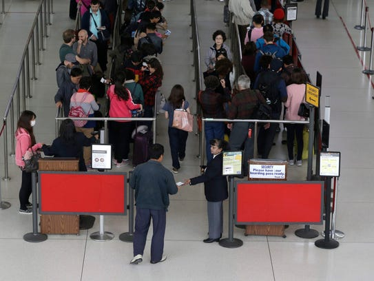 epa04438555 Passengers wait in line at Transportation