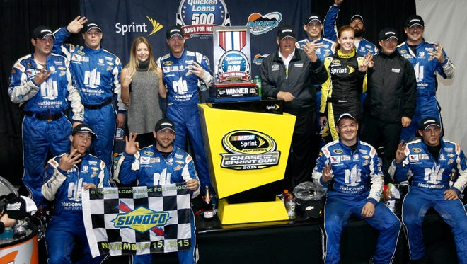 Dale Earnhardt Jr., center left, and his pit crew celebrate their third victory of the season after winning the NASCAR Sprint Cup Series auto race at Phoenix International Raceway, Sunday, Nov. 15, 2015, in Avondale, Ariz. Earnhadrt was leading on lap 219 when the race was called due to rain.