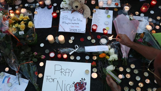 People gather and place tributes on the Promenade des Anglais on July 15, 2016.