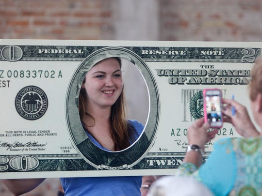 Liz Bovay poses with the $20 bill someone brought to the town hall meeting.  Taking her photo was her grandmother Jean Gilroy of Seneca Falls.