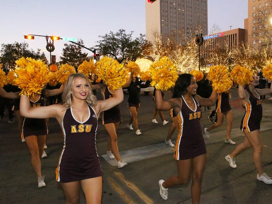 Carson Edwards, left, and the Arizona State cheerleaders march along Oregon Street with the Sun Devils band Thursday.