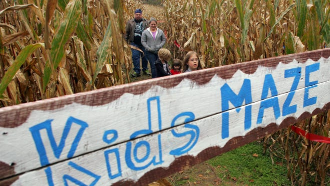 Brian Perkins and Rachael Yoder walk with their children through the children portion of McPeek's Mighty Maze at Colonial Campground on County Road 10.