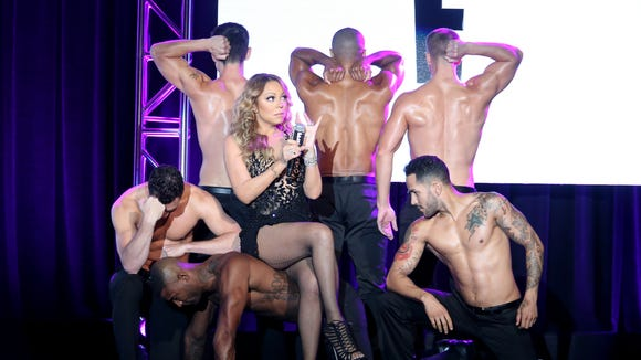 Mariah and her muscled entourage.