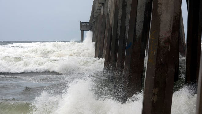 Waves generated by Tropical Storm Cindy crash into the Pensacola Beach Fishing Pier as the storm churns in the Gulf of Mexico on Tuesday, June 20, 2017.