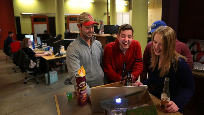 Jeremy Graham, from left, Adam Stillman and Emily Pokoik enjoy a stadium hole golf video at the LockerDome company headquarters on Washington Avenue in downtown St. Louis. The social media firm is growing rapidly.