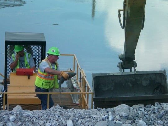 Workers find dead fish in the Emory River during cleanup.