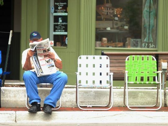 Jerry Cole of Port Huron finds a seat along Huron Avenue to sit and read a newspaper before all the excitement of the Rotary International Day Parade begins a few hours later.