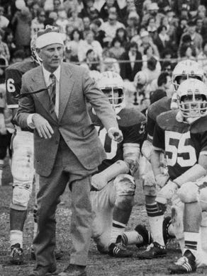 Brick head coach Warren Wolf, wearing a Santa Claus hat, with his players on the field in anundated photo.