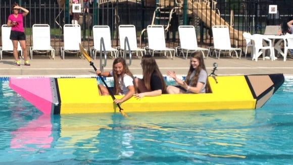 Kaela Wilson, Hannah Miller and Paige Waite ride in the cardboard boat they designed.
