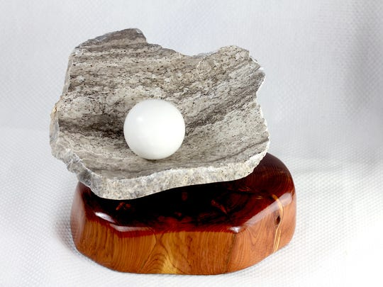 A sculpture by Eric Ferguson of wood and stone bringing lines, form, and shape together