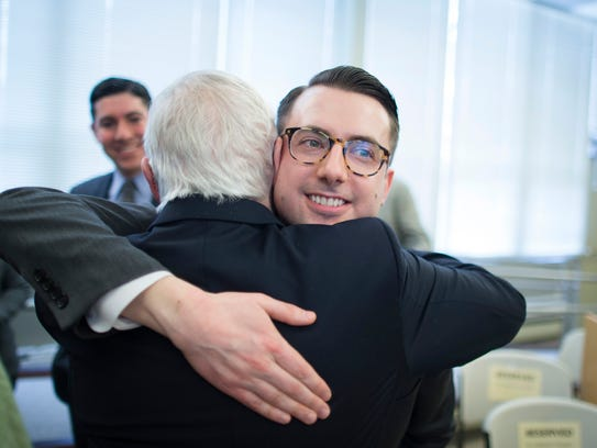Thomas Rimbey Ogletree, center right, hugs his father, Rev. Thomas Ogletree, following a news conference to announce that a case against Ogletree for breaking church law by officiating his son's same-sex marriage had been dropped, Monday in White Plains, N.Y.