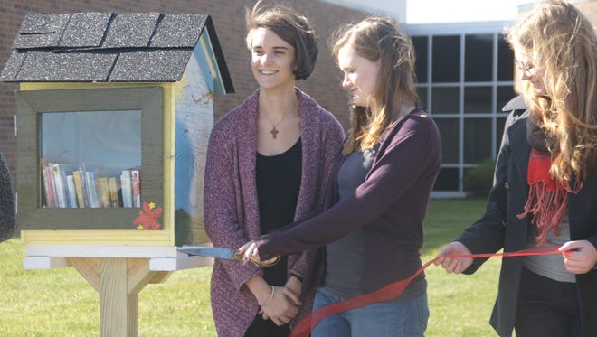 Emily Neuendorf (left), Tess Barnett and Elizabeth May installed three Little Free Libraries at elementary schools in Hancock County.