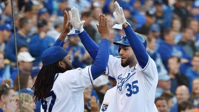 Royals first baseman Eric Hosmer celebrates with starting pitcher Johnny Cueto after scoring a sixth-inning run in Game 2.