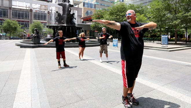 John Drury leads his wife, Lori, and their sons Peyton and Kori in some Zumba moves at Fountain Square in June. On Saturday he will host a dance-a-thon on Fountain Square in honor of his mother, who was killed by a drunk driver earlier this year.