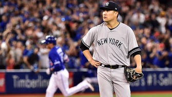 New York Yankees starting pitcher Masahiro Tanaka (19) reacts after giving up a grand slam to Toronto Blue Jays shortstop Ryan Goins (17) rounding the bases during the sixth inning of a baseball game, Friday, Sept. 22, 2017 in Toronto.