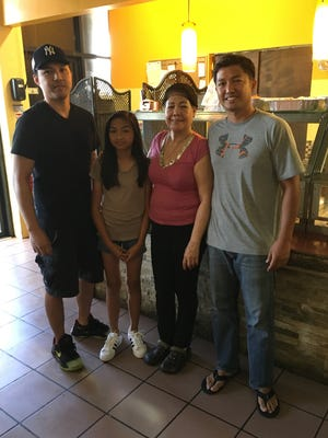 Members of the Calalo family surround Teresita Calalo at the family's Nayon Express Restaurant in Harmon, Dededo, on Dec. 22, 2017. The restaurant is up for sale as the family looks to help Teresita retire. Pictured, from left: son Maynard Calalo, granddaughter Abigail Calalo, Teresita Calalo, and son Galvin Calalo.
