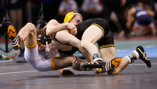 Wyoming's Tyler Cox, rear, wrestles Iowa's Cory Clark, front, in a 125-pound match in the second round of the NCAA Division I wrestling championships in Oklahoma City, Thursday, March 20, 2014. (AP Photo/Sue Ogrocki)