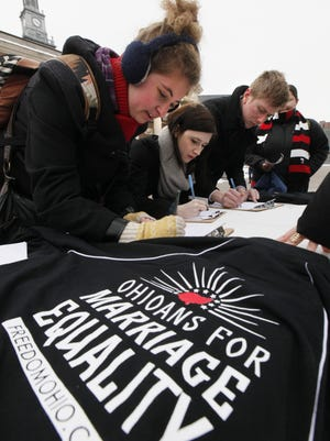 From left, Samantha Stephenson, Sarah Jewell and Peter Oehrtman were among the people who signed a ballot inattentive for gay marriage, Ohioans for Marriage Equality was on the campus of the University of Cincinnati gathering signatures on Feb. 14, 2014.