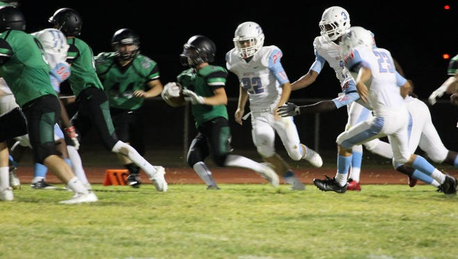 Virgin Valley's Jaret Tietjen, center, looks for running room during a kickoff return during the Bulldogs' home win last week against Western.