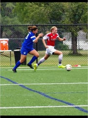 Michigan Hawks midfielder Courtney Petersen (right) outruns an opponent during a club soccer contest.