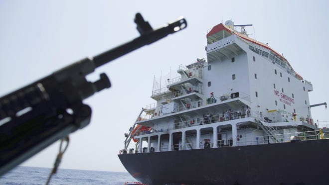 """Sailors stand on deck above a hole the U.S. Navy says was made by a limpet mine on the damaged Panama-flagged, Japanese owned oil tanker Kokuka Courageous, anchored off Fujairah, United Arab Emirates, during a trip organized by the Navy for journalists, Wednesday, June 19, 2019. The limpet mines used to attack a Japanese-owned oil tanker near the Strait of Hormuz last week bore """"a striking resemblance"""" to similar mines previously seen in Iran, a U.S. Navy explosives expert said Wednesday, stopping short of directly blaming Tehran for the assault. (AP Photo/Fay Abuelgasim)"""