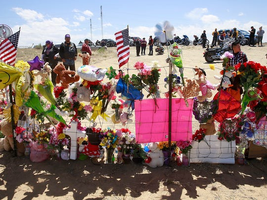 Riders who were part of a funeral procession for Ashlynne Mike pause at the roadside memorial on May 6 in Lower Fruitland.