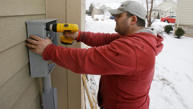 A construction worker installs an electrical box on a new home in Pepper Pike, Ohio.