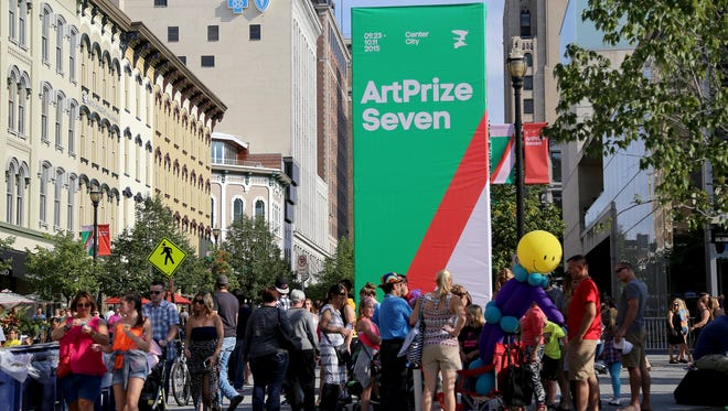 Families enjoy the festive atmosphere near the Grand Rapids Art Museum during ArtPrize Seven in Grand Rapids.
