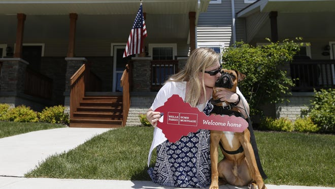 Michele Lammers gives her service dog, Titus, a big kiss Monday, June 1, 2015, after receiving the keys to her new home in West Des Moines. Lammers, an Army Reserve Chief Warrant Officer who joined the Army in 1998, received the mortgage-free home from Wells Fargo and the Operation Homefront program.