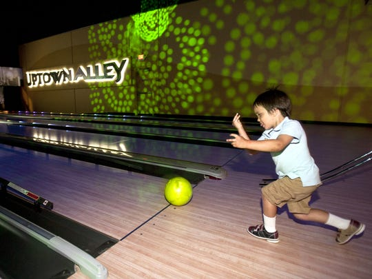 A little boy has loads of fun bowling at Uptown Alley