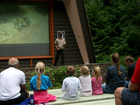 Park visitors watch a park ranger give an evening presentation