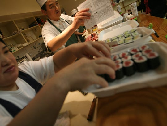 Fujie Welch, left, assembles take-out orders of sushi